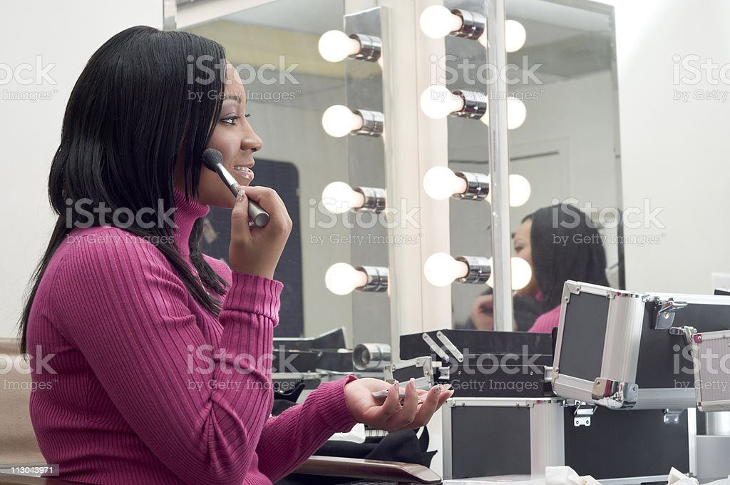 Young woman applying makeup, looking at mirror royalty-free stock photo