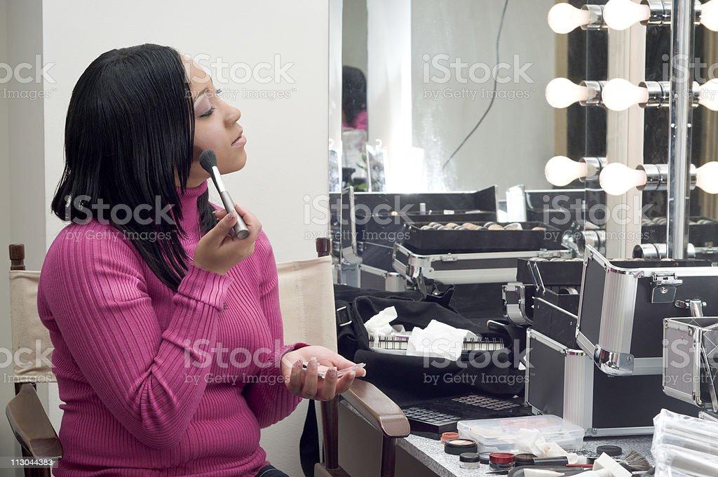 Young woman applying makeup, looking at mirror royalty-free stock photo