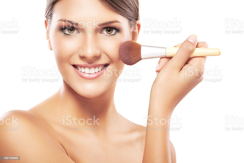 Young woman applying makeup on face stock photo