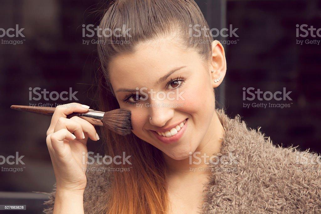 Young woman applying makeup stock photo