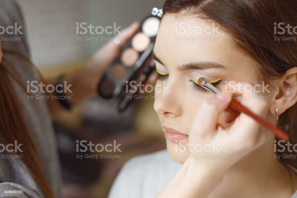 Young woman applying makeup to model in salon stock photo