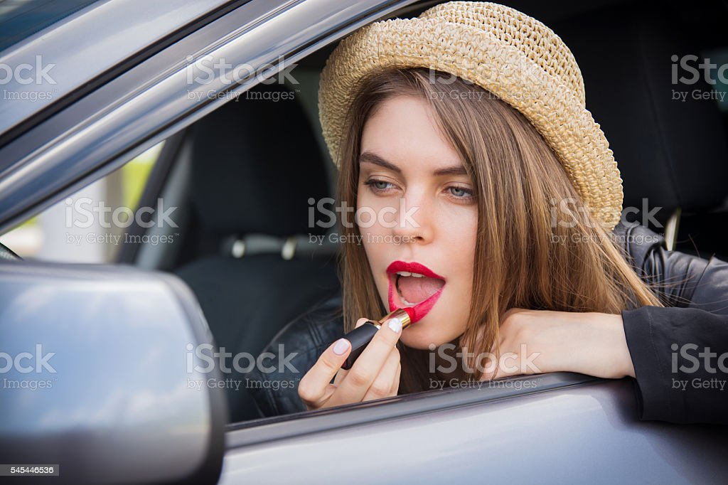 Young woman applying makeup while in the car stock photo