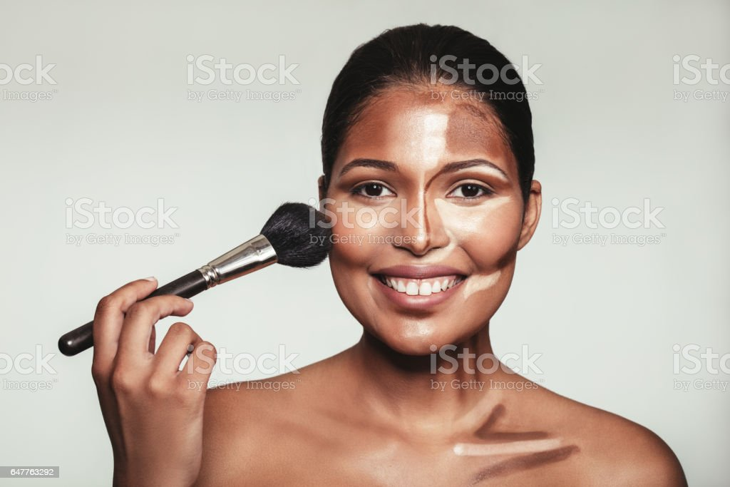 Young woman applying makeup with brush. stock photo
