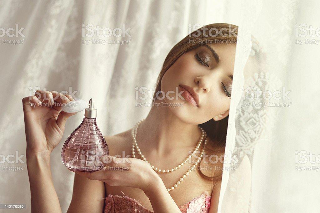 young woman applying perfume stock photo