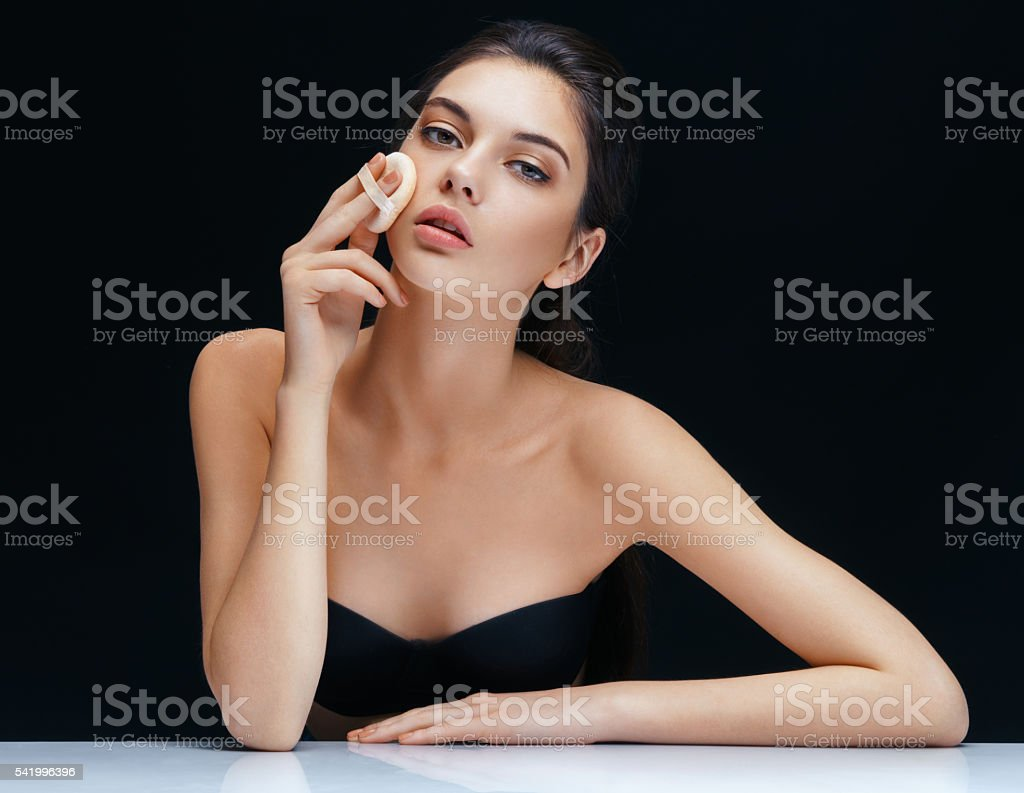 Young woman applying powder on her face stock photo