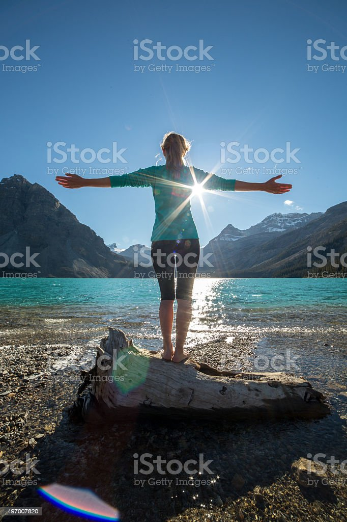 Young woman arms outstretched by the lake embracing life stock photo