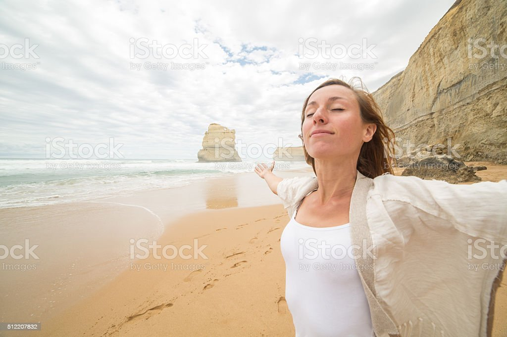 Young woman arms outstretched on Gibsons steps beach, Australia stock photo