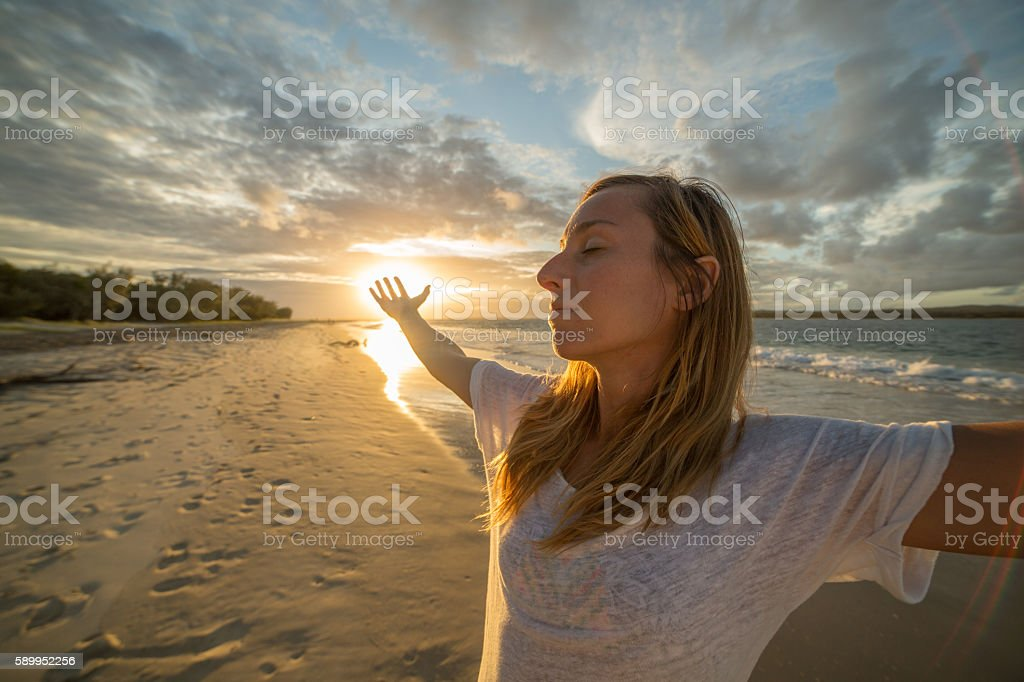 Young woman arms outstretched on the beach at sunset stock photo