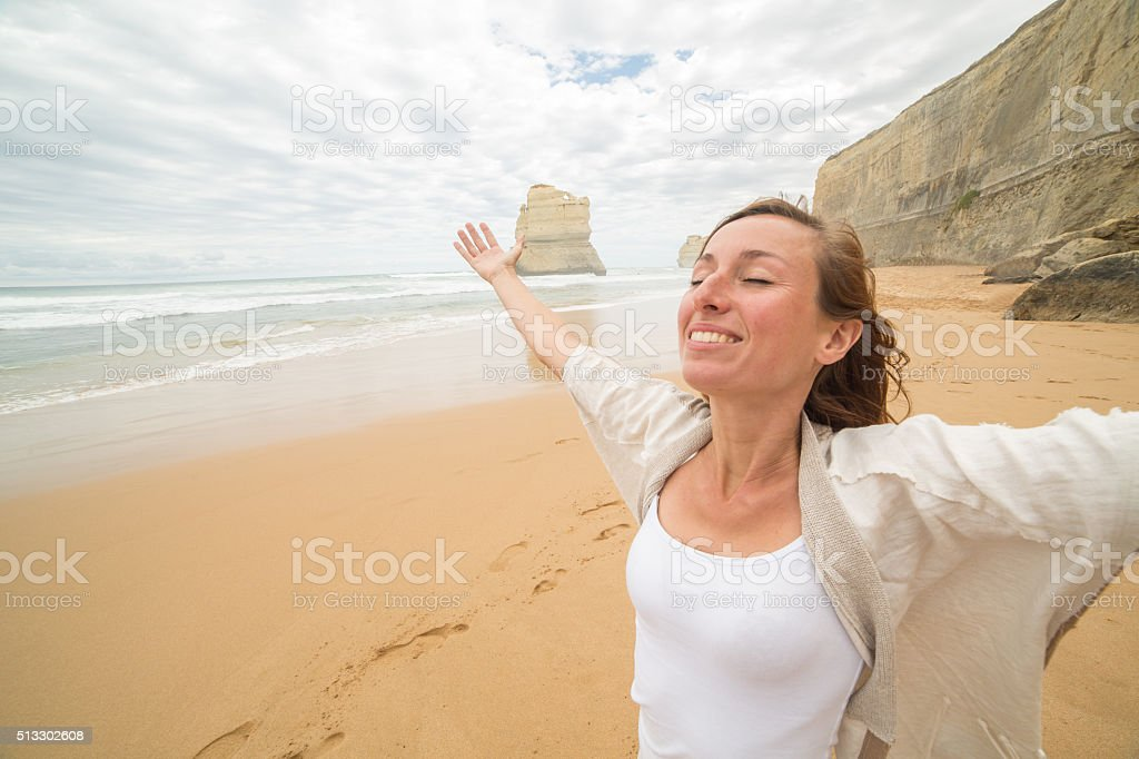 Young woman arms outstretched on Twelve apostles beach-Great Ocean Road stock photo