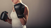 Young woman arms wear boxing gloves.