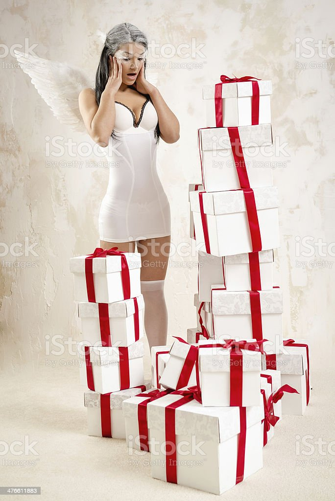 Young woman as angel with heap of gift boxes royalty-free stock photo