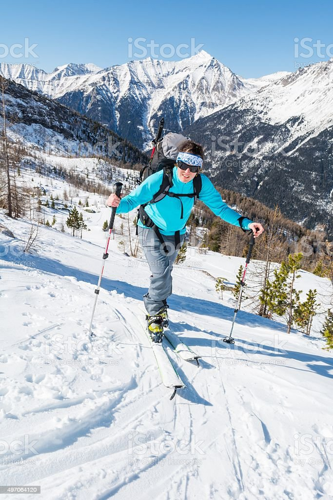 Young woman ascending a slope on skis. stock photo