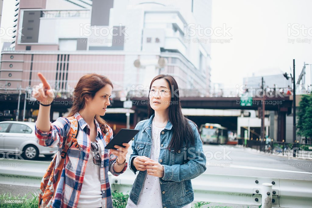 Young woman asking for direction on street stock photo