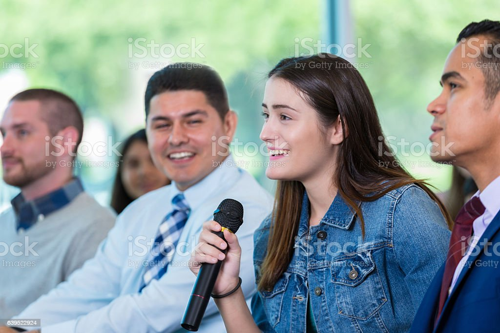 Young woman asks question during town hall meeting stock photo