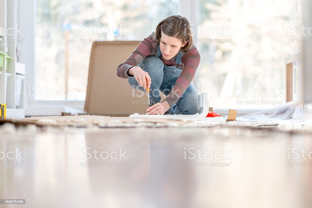 Young Woman assembling a DIY furniture at home stock photo