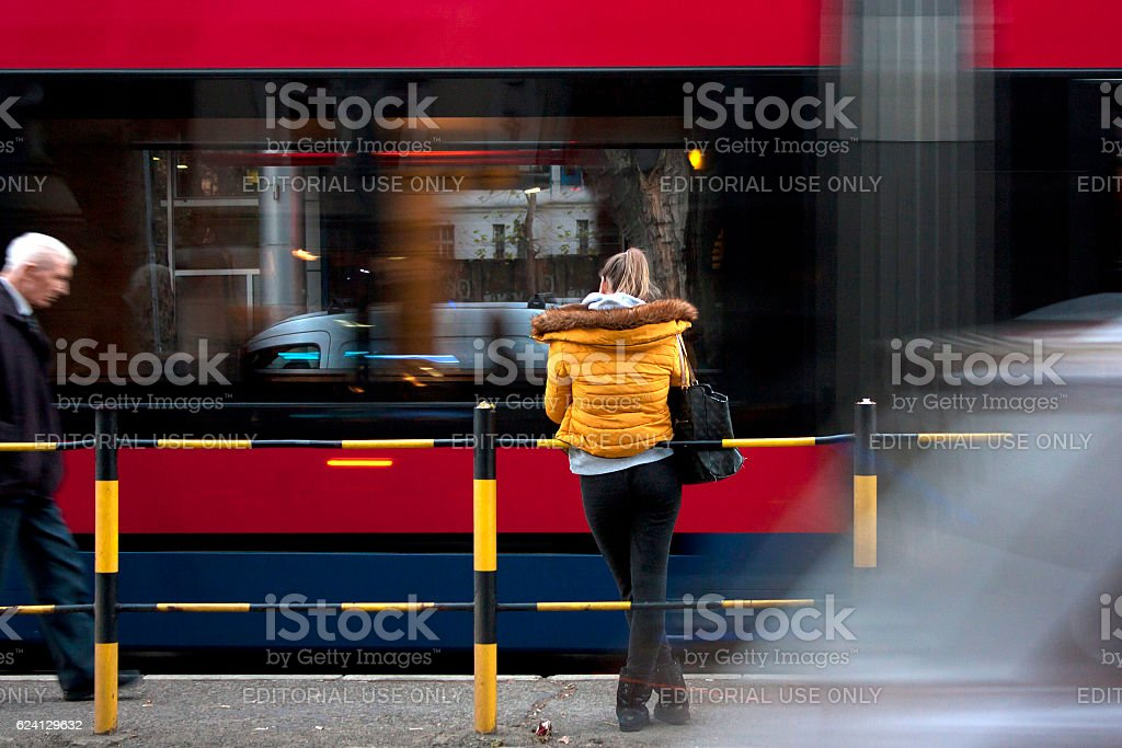 Young woman at a bus stop stock photo