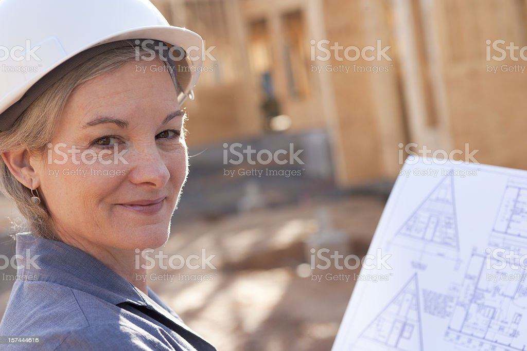 Young woman at a construction site holding blueprints royalty-free stock photo