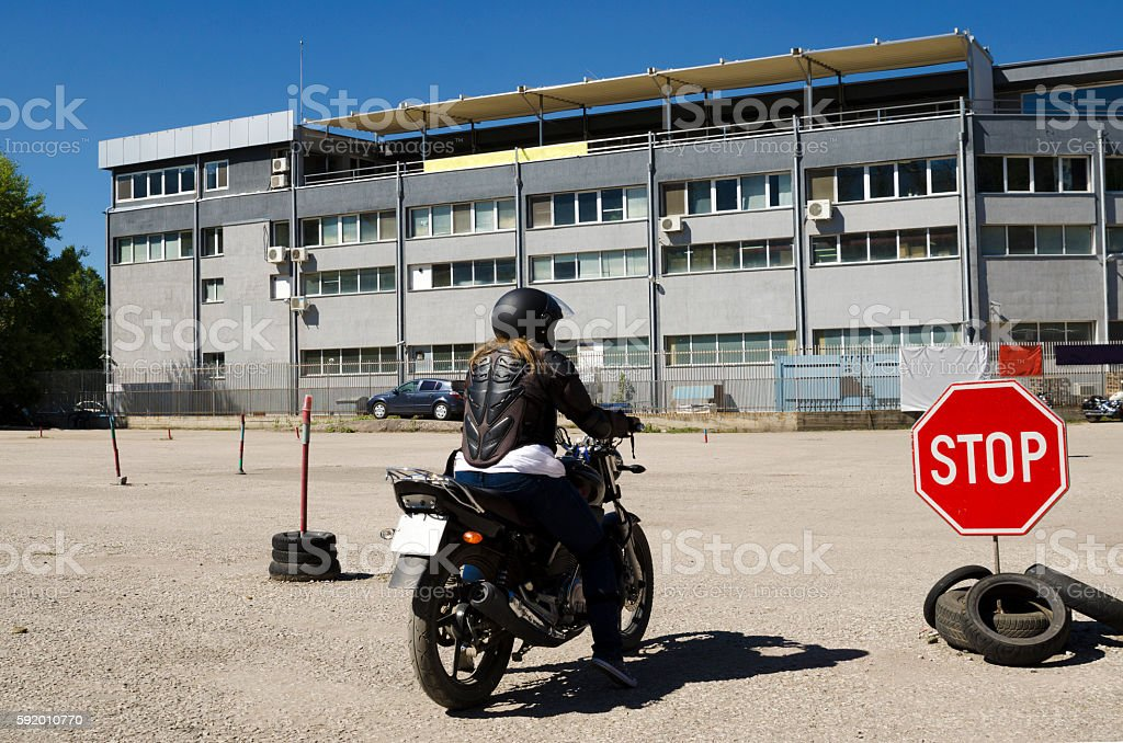 Young woman at a motorcycle in a course stock photo