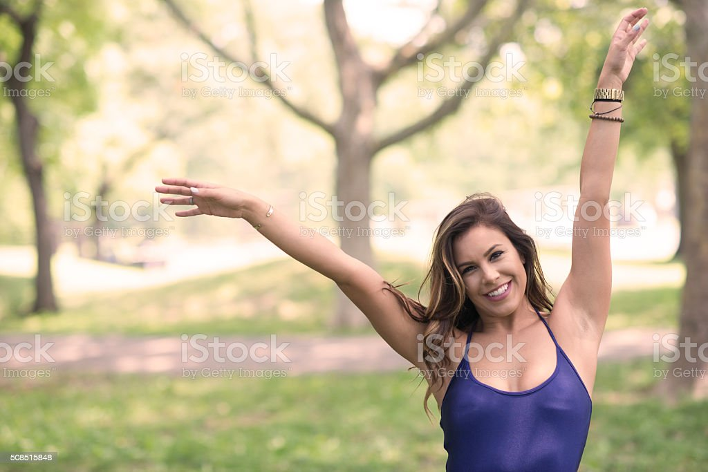 Young woman at a park with arms up stock photo