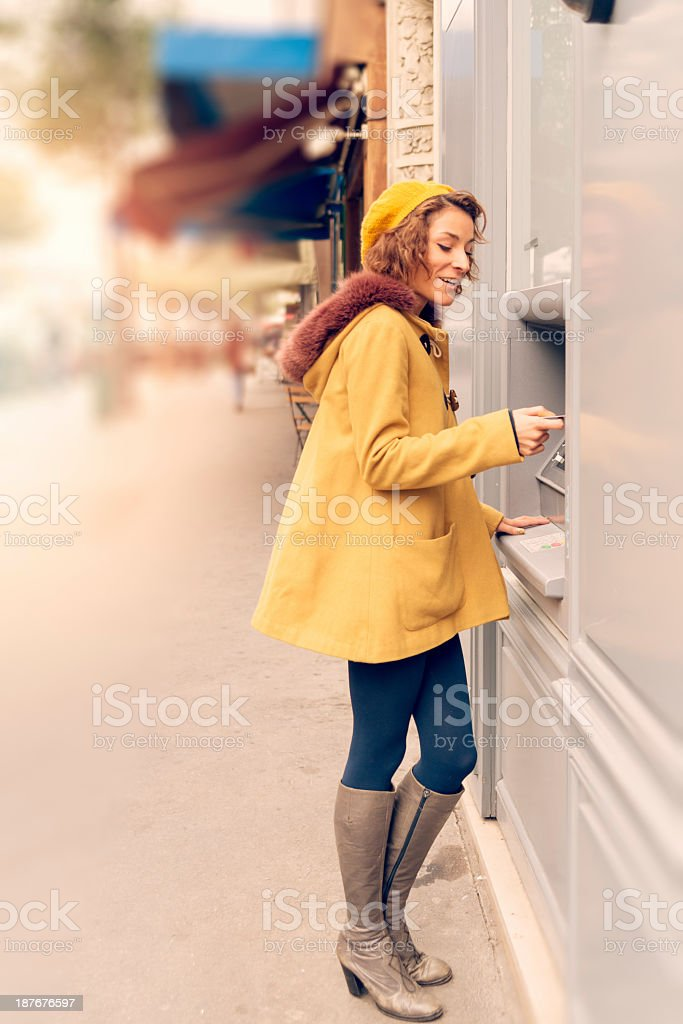 Young woman at ATM machine on street. royalty-free stock photo