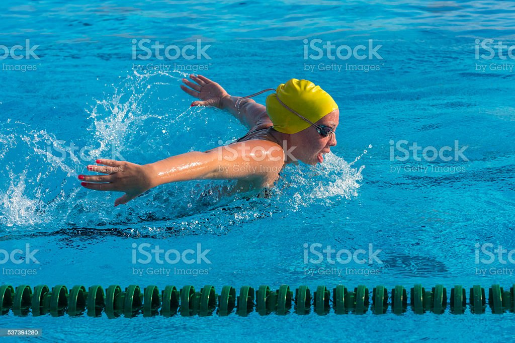 Young woman at butterfly stroke stock photo