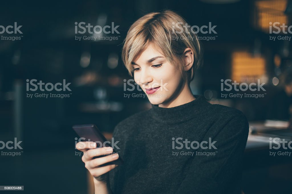 Young woman at cafe using her mobile phone stock photo
