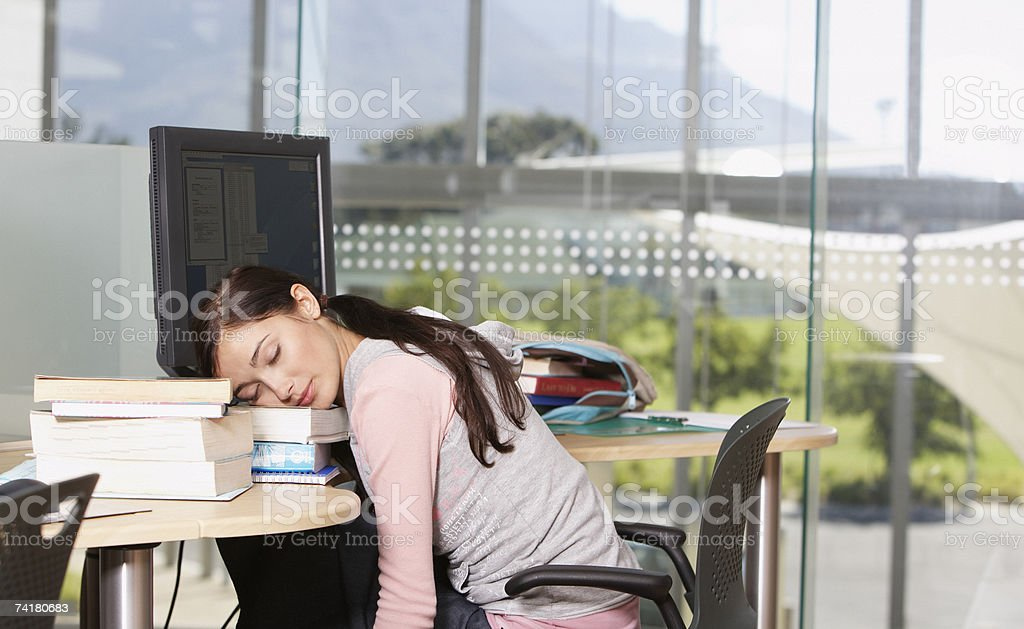 Young woman at computer with books sleeping royalty-free stock photo