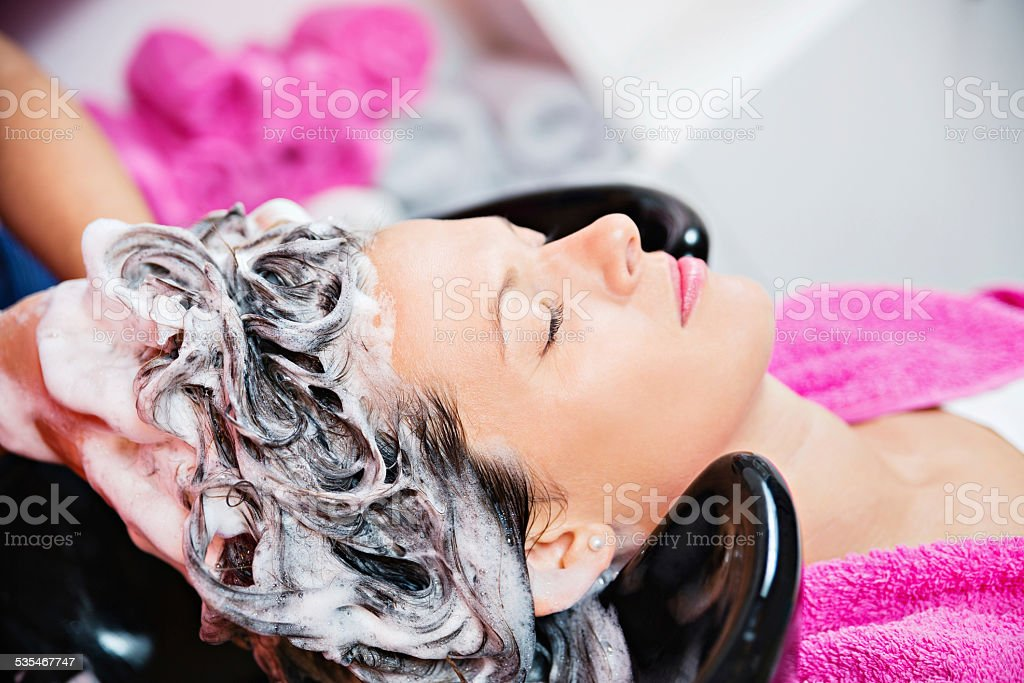 Young Woman At Hairdresser Washing Her Hair stock photo