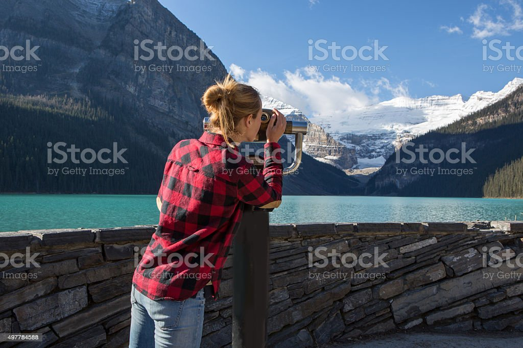 Young woman at lake Louise looking at view from viewfinder stock photo