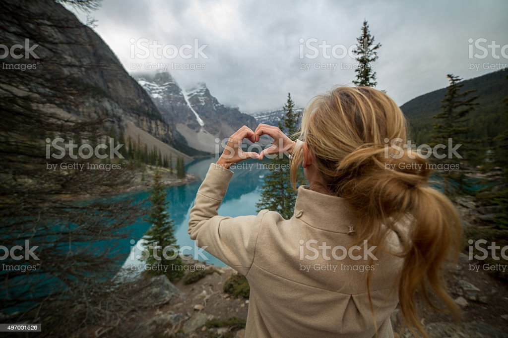 Young woman at Moraine lake makes a heart shape frame stock photo