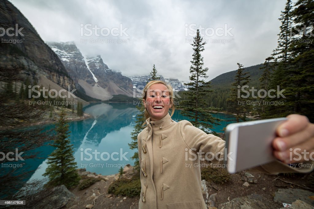 Young woman at Moraine lake taking a selfie portrait stock photo