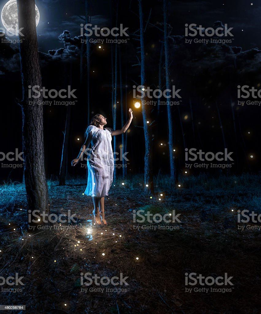 young woman at night forest with full moon jumping high stock photo
