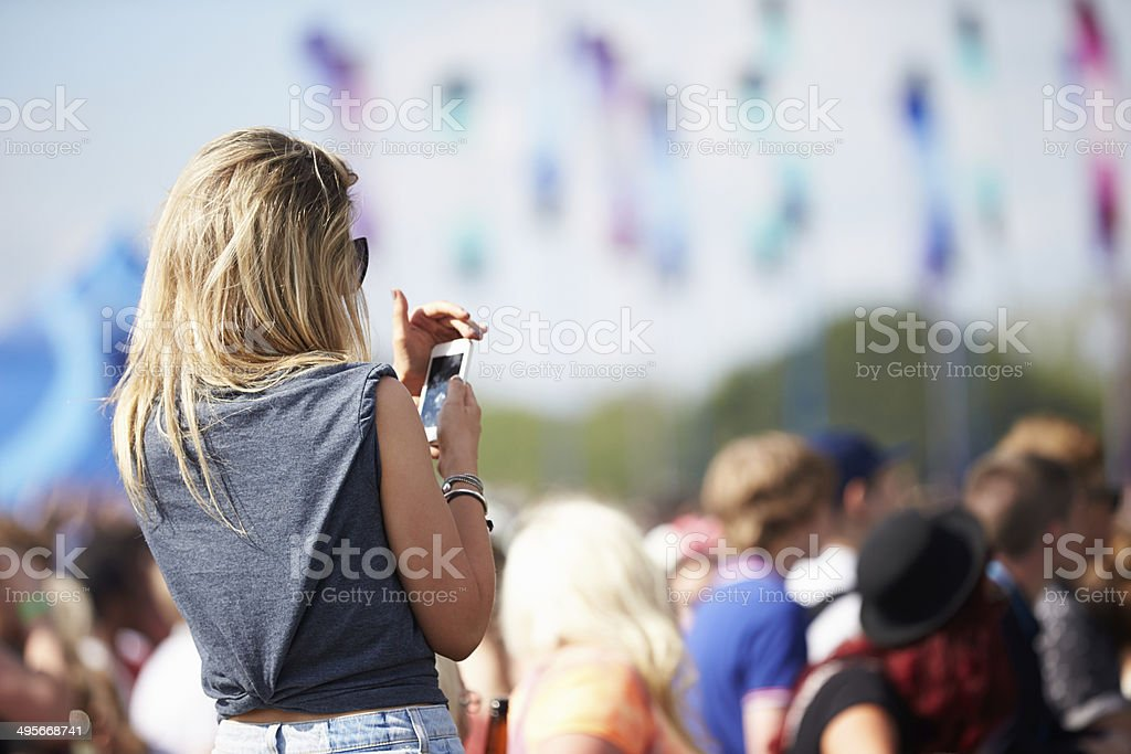 Young Woman At Outdoor Music Festival Using Mobile Phone stock photo