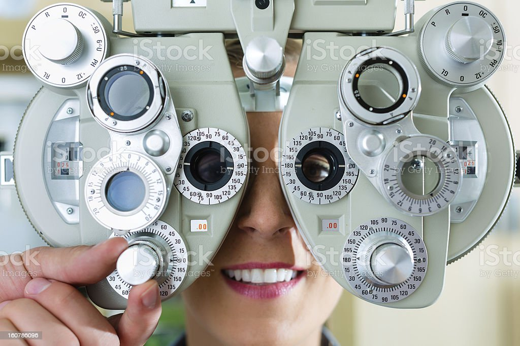Young woman at phoropter for eye test stock photo