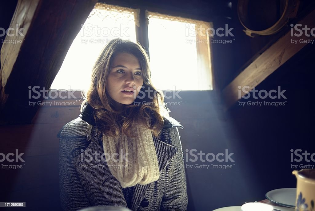 Young Woman at Table in Wooden Chalet royalty-free stock photo