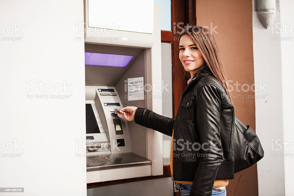 Young woman at the ATM machine stock photo