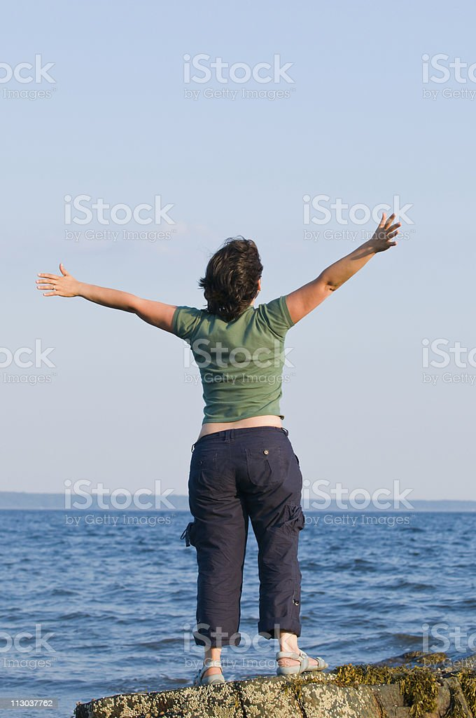 Young woman at the beach with arms outstretched royalty-free stock photo