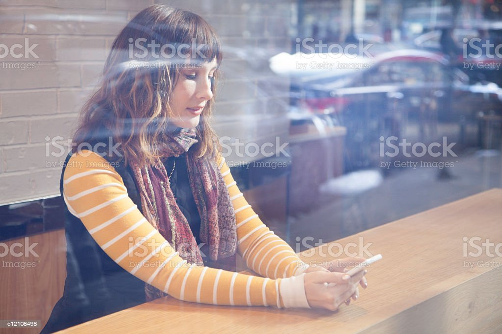 Young Woman at the cafe with her Mobile Phone stock photo