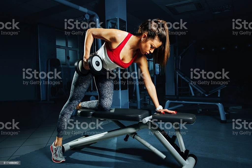 Young woman at the gym back workout with dumbbells stock photo