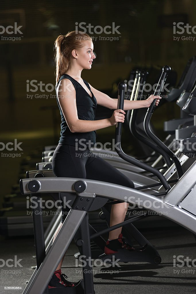 Young woman at the gym exercising. Run on machine stock photo