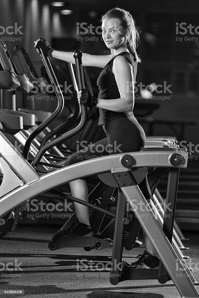 Young woman at the gym exercising. Run on machine. stock photo
