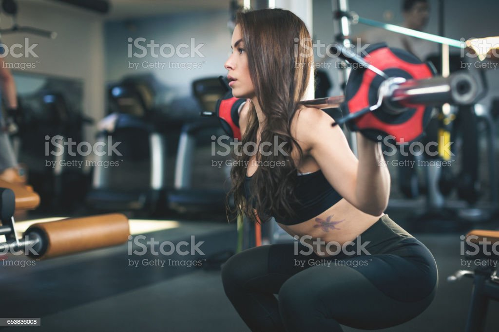 Young woman at the gym lifting weights stock photo