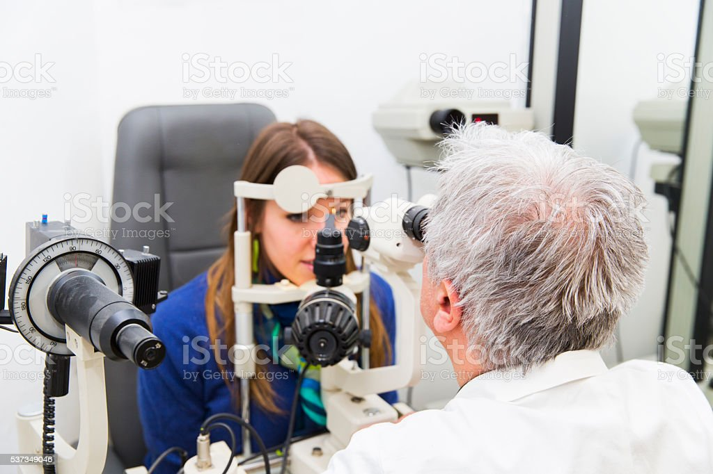 Young woman at the optometrist,doctor is checking her vision stock photo