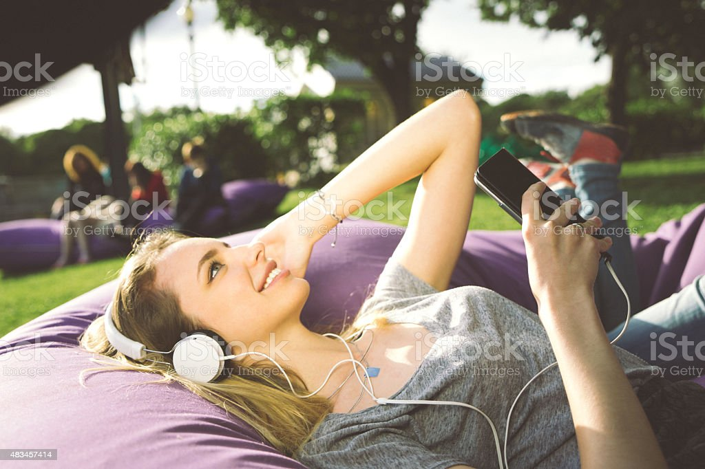 Young Woman At The Park, Listening To Music And Relaxing stock photo