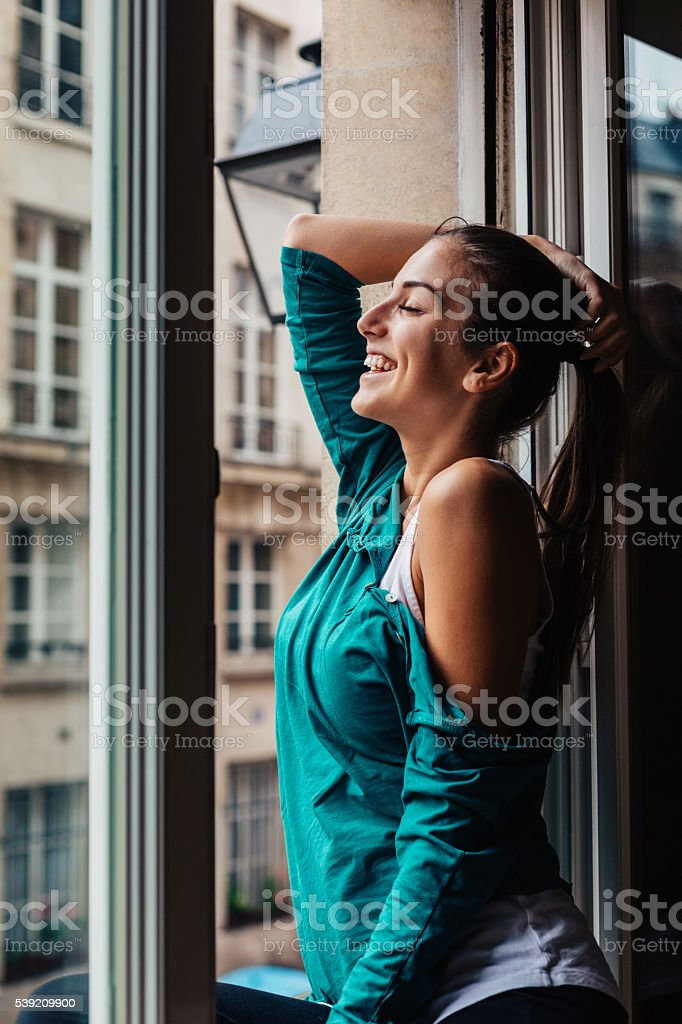 Young woman at the window in the morning stock photo