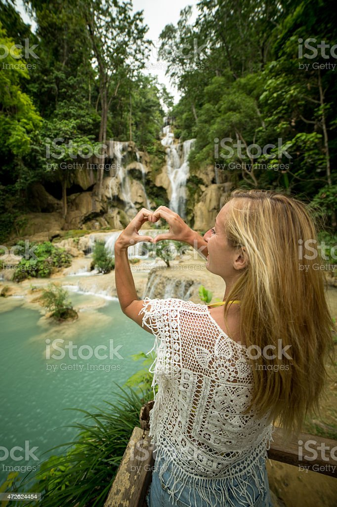 Young woman at waterfalls making heart shape with hands stock photo
