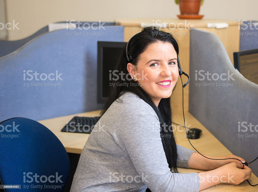 Young woman at work speaking in microphone headset  and smiling stock photo