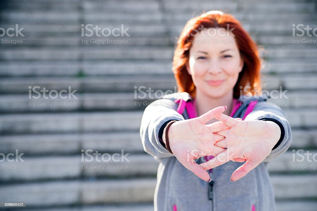 Young woman athlete stretching outdoors stock photo
