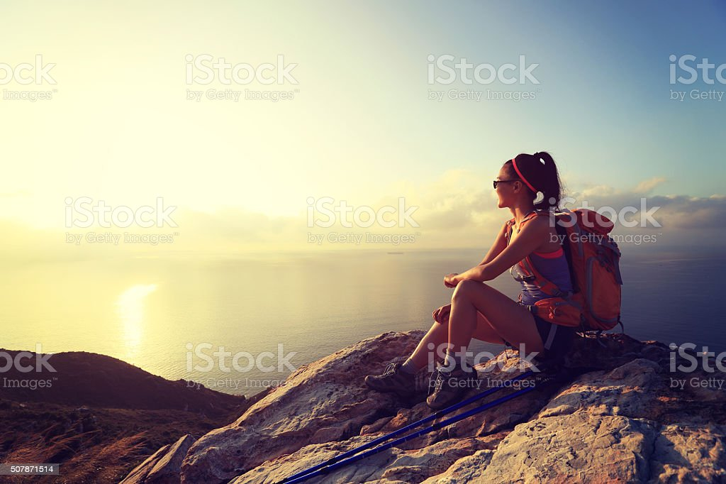 young woman backpacker at sunrise seaside mountain peak stock photo