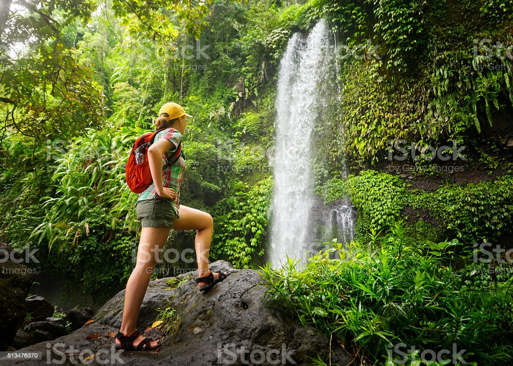 young woman backpacker looking at the waterfall in jungles. stock photo